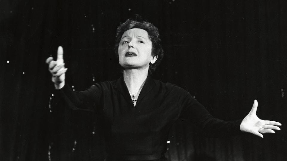 La chanteuse Édith Piaf, en performance, les mains tendues de chaque côté de son corps.