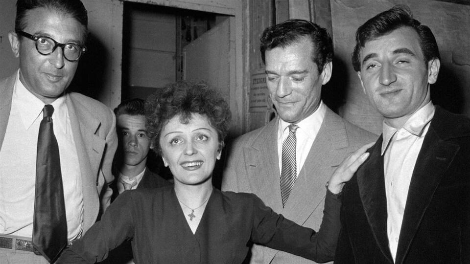Édith Piaf pose avec Michel Emer (à gauche) et Eddie Constantine et Charles Aznavour (à droite)