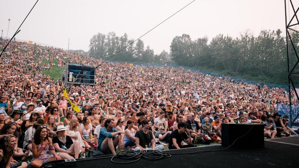 Des milliers de personnes assisent devant une scène de concert.