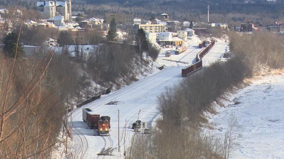 Des policiers examinent les lieux de l'accident sur une voie ferrée, près d'une locomotive et de wagons immobilisés.