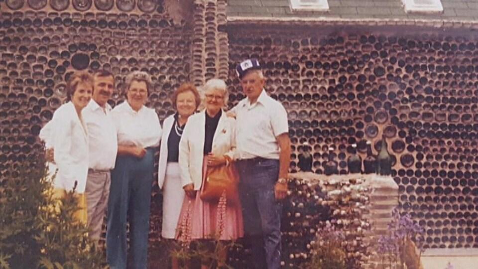 Photo des années 1980 avec un groupe de personnes, dont Édouard Arsenault, devant une maison de bouteilles.
