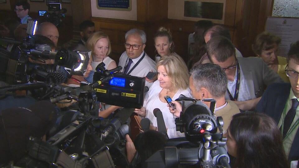 Lisa Thompson, la ministre de l'Éducation de l'Ontario, entourée de journalistes.
