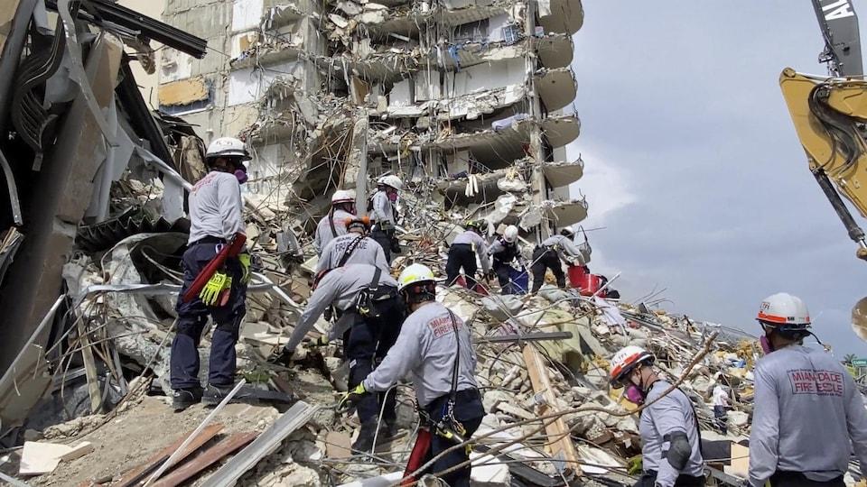 Rescuers climb on piles of debris.