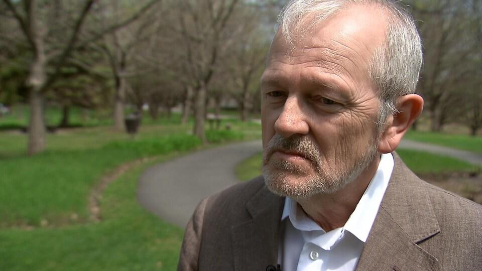 Égide Royer répond aux questions d'un journaliste dans un parc.