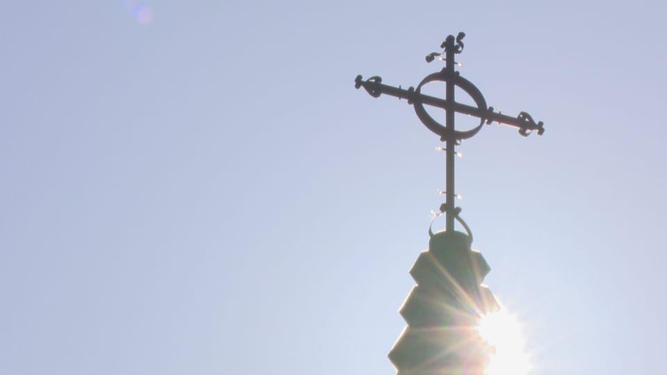 Une photo contre jour d'une croix au sommet d'une église. Le soleil brille derrière. Le ciel est bleu.