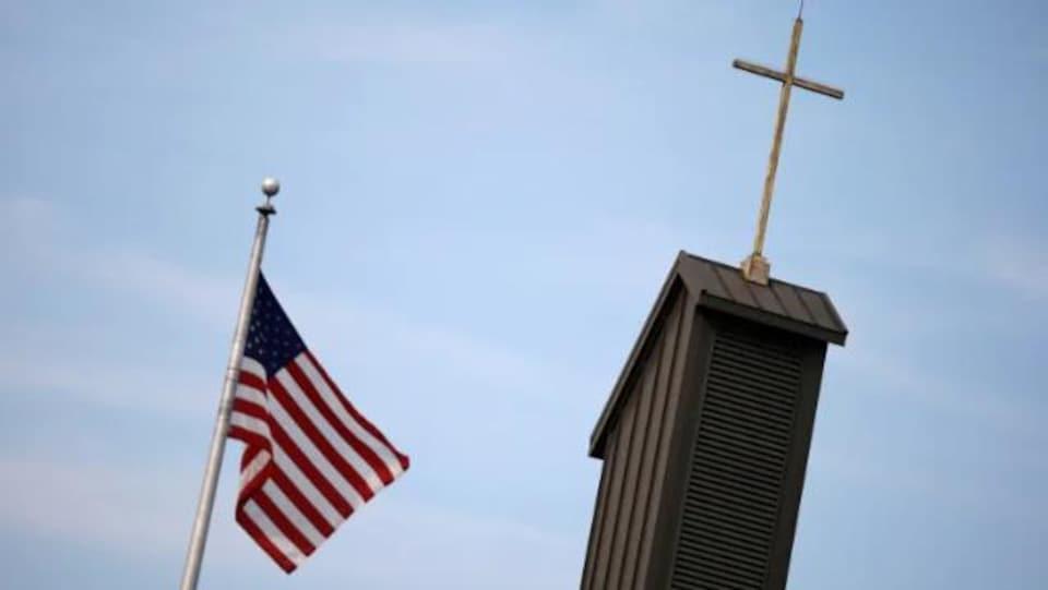 le drapeau des états-unis flotte dans les airs à côté de la croix de l'église cahtolique