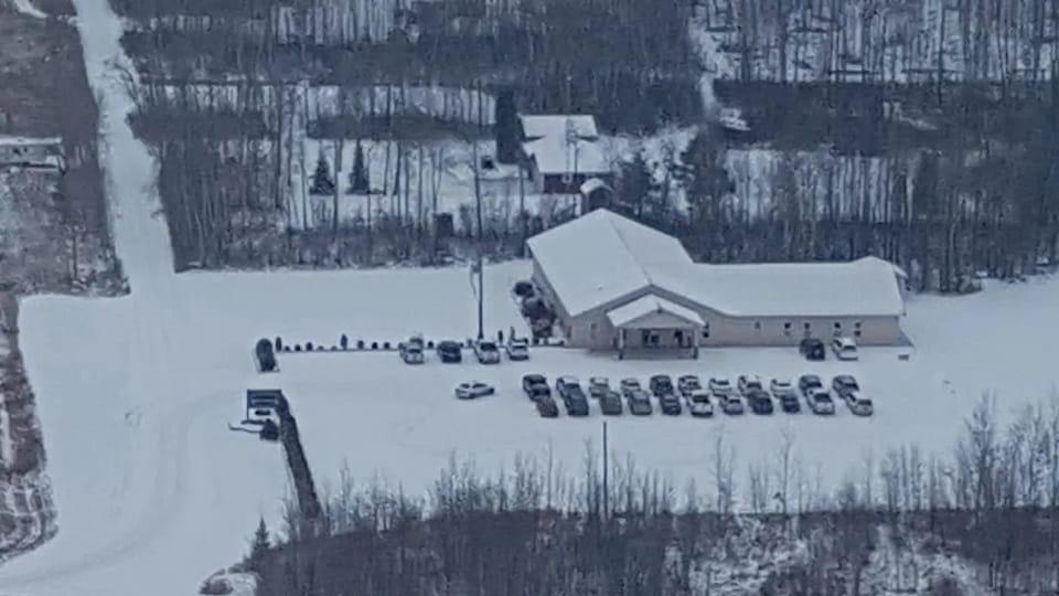 L'église, vue de haut, avec un stationnement rempli d'une vingtaine de voitures.