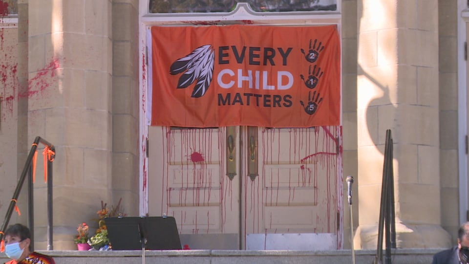 Façade de l'église recouverte de peinture rouge et avec un drapeau inscrit Every Child Matters.