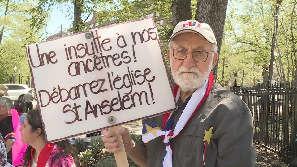 Un manifestant à Halifax le 9 juin 2019 avec une affiche sur laquelle est écrit : « Une insulte à nos ancêtres ».