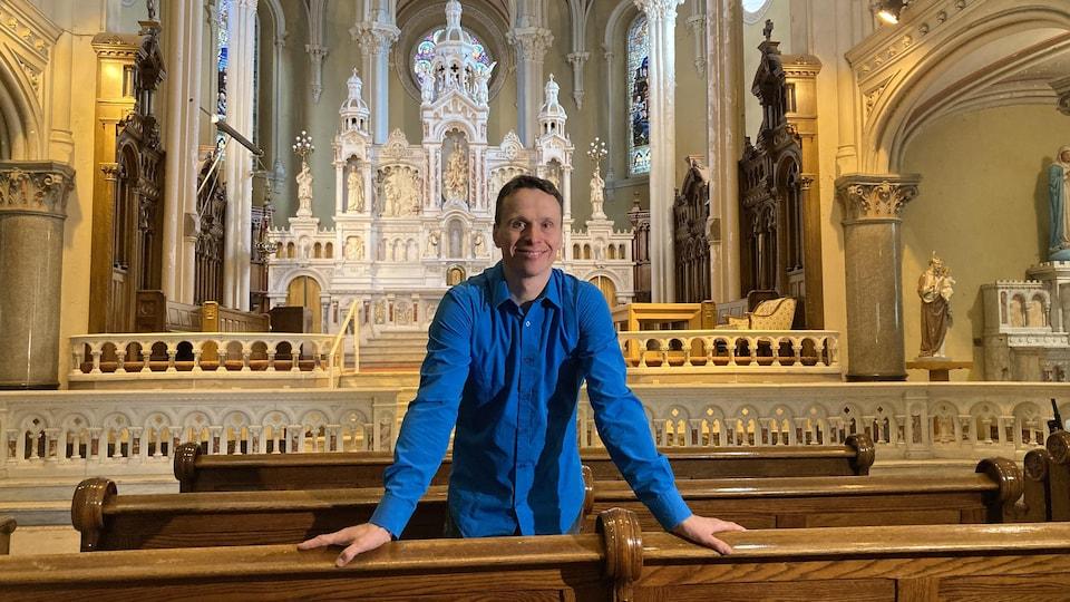 Un homme vêtu d'une chemise bleue devant l'autel de l'église Saint-Charles-de-Limoilou.