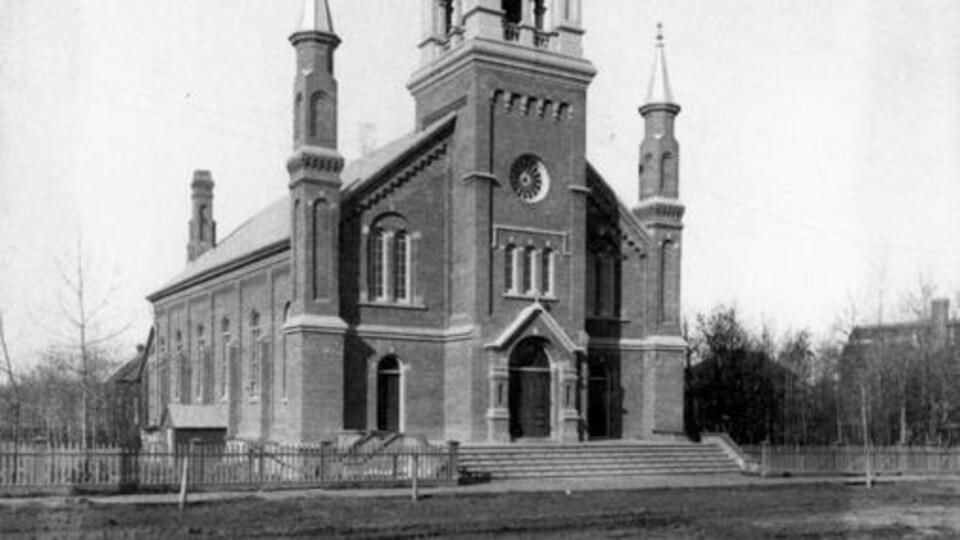 Photo d'archives en noir et blanc qui montre la façade et le flanc de l'édifice.