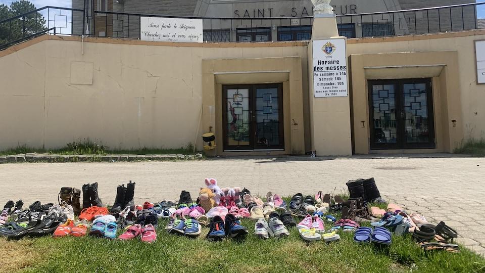 Des souliers d'enfants ont été déposés devant l'église Saint-Sauveur en hommage aux enfants du pensionnat de Kamloops.