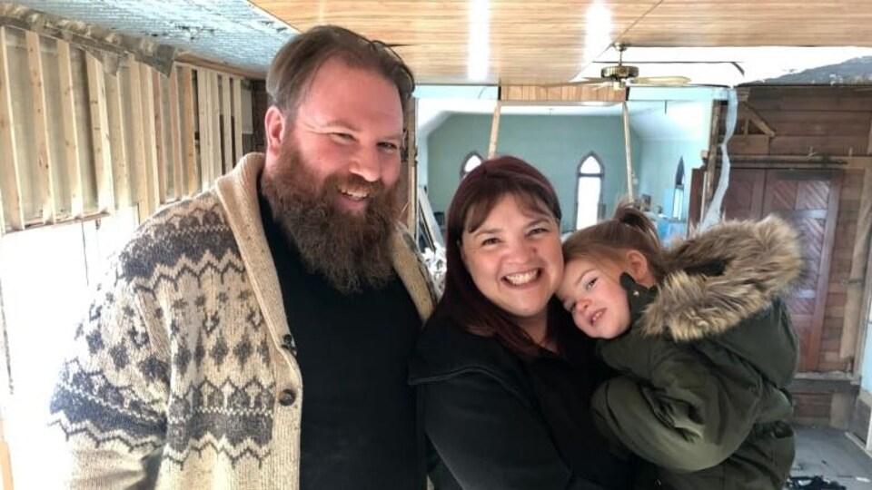 Un couple, avec un jeune enfant, sourient au sein du ancienne église en très mauvais état.