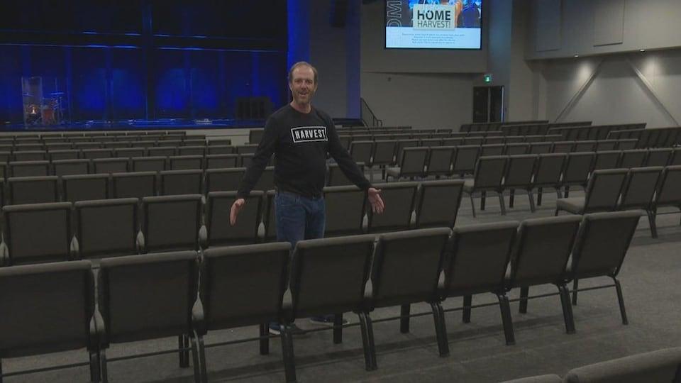 Un homme montre trois chaises de ses mains