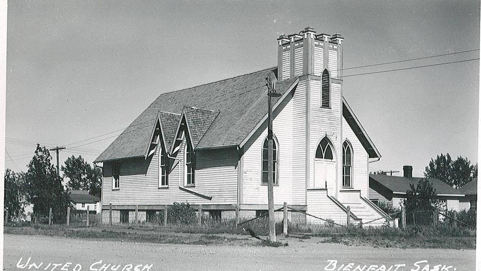 Vieille photo d'une église en bois dans un quartier résidentiel.
