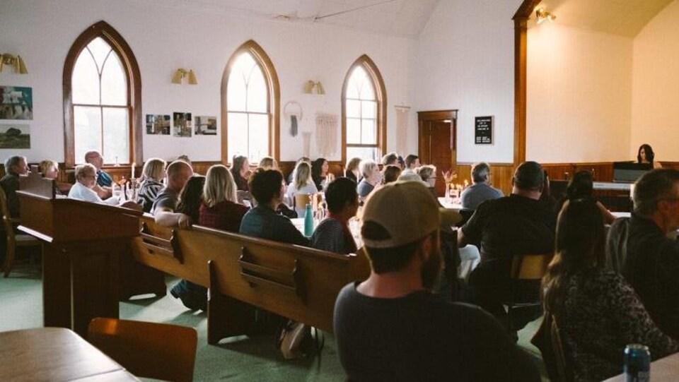Des gens assistent à un concert, assis dans une église.