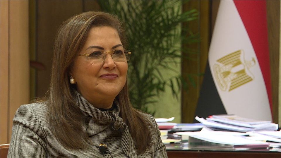 On voit Mme El-Saïd dans son bureau, souriant à la caméra. En arrière-plan, des documents sur une table et le drapeau égyptien.