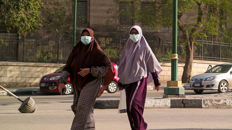 On voit deux femmes traversant une rue. Elles portent un masque chirurgical.