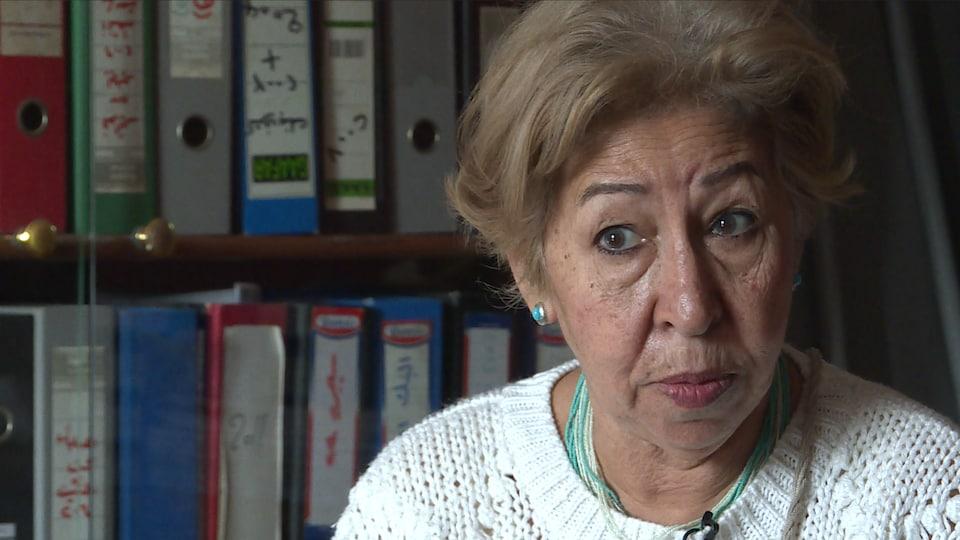 On voit Mme Hadi qui parle à la caméra. En arrière-plan, des classeurs dans une bibliothèque.