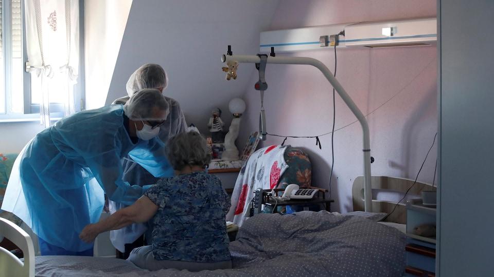 Deux personnes soignantes portant des vêtements protecteurs et un masque avec une aînée dans une chambre d'hôpital.