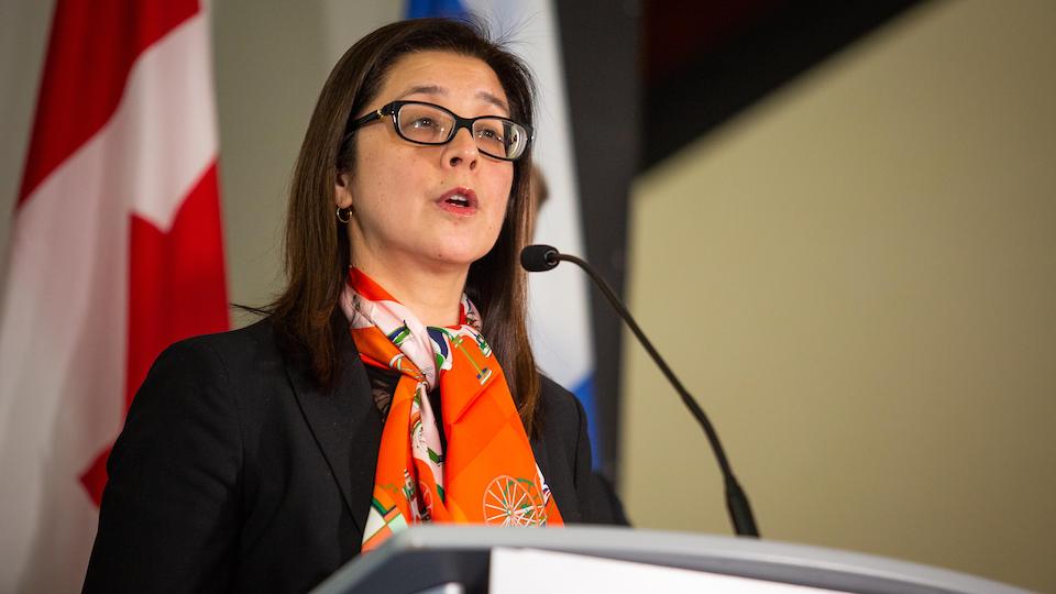 Une femme avec un foulard orange devant un podium.