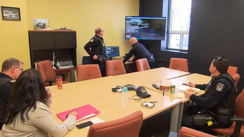 Des policiers autour d'une table dans une salle de réunion.