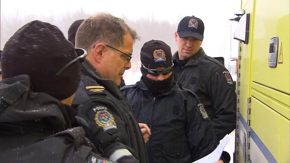 Le sergent est entouré de quelques policiers.
