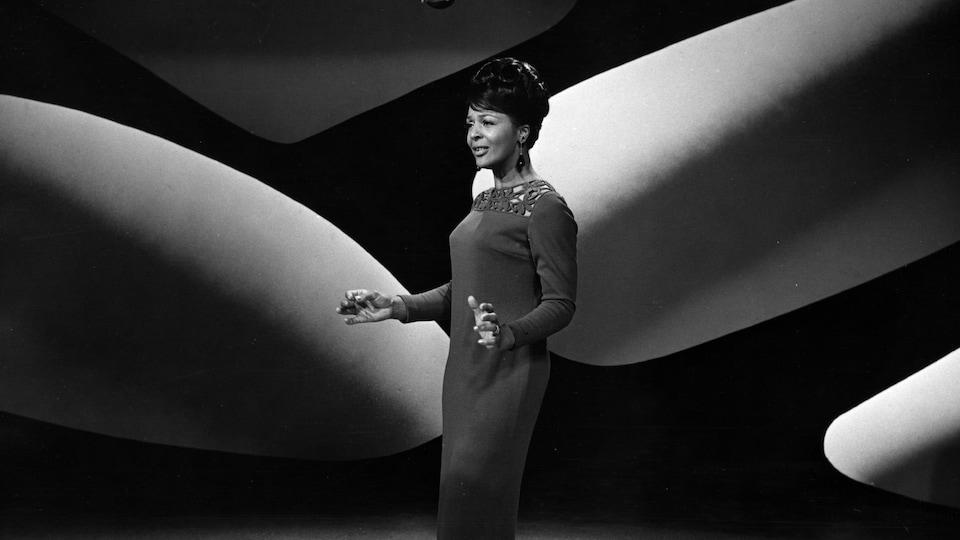 Eleanor Collins en 1966 debout sur une scène, portant une robe longue.