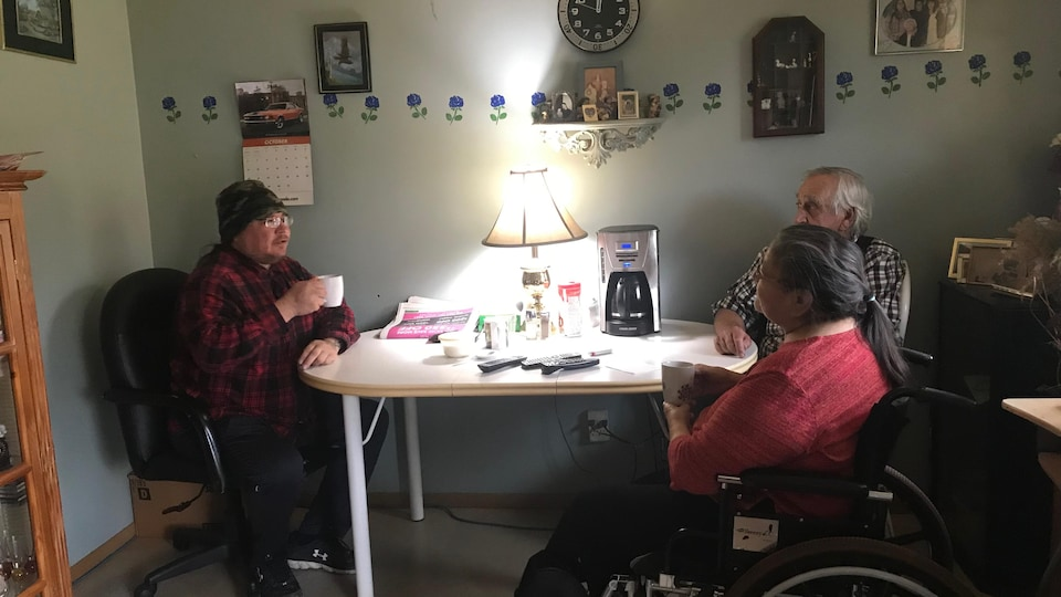 Des gens sont assis autour d'une table, boivent un café et discutent.