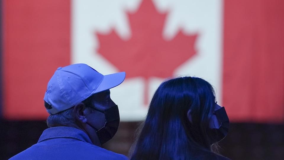 Des électeurs devant un drapeau du Canada.