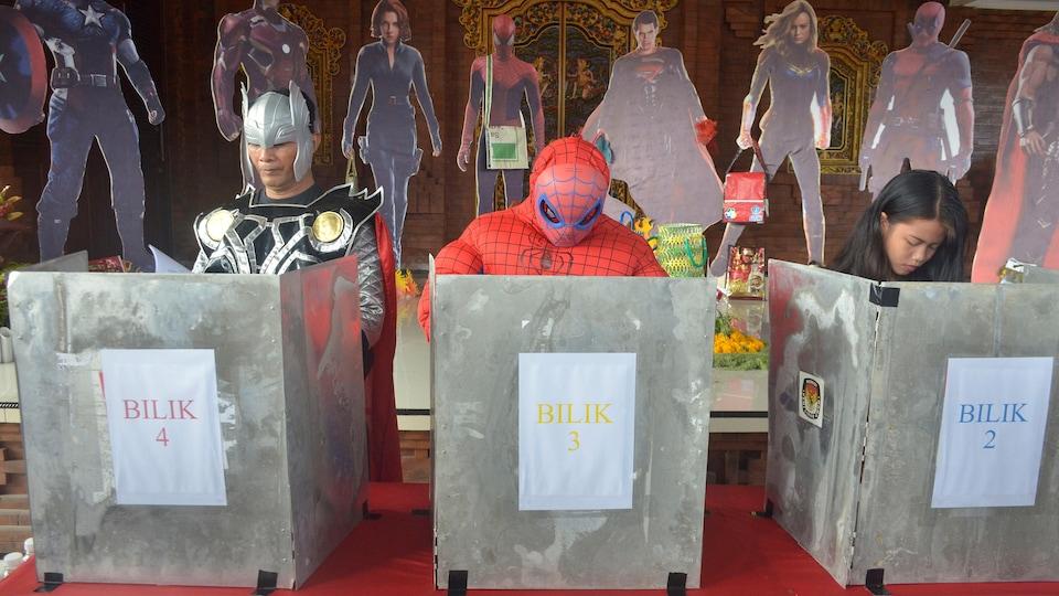 Des électeurs déguisé en super héros votent dans des isoloirs.