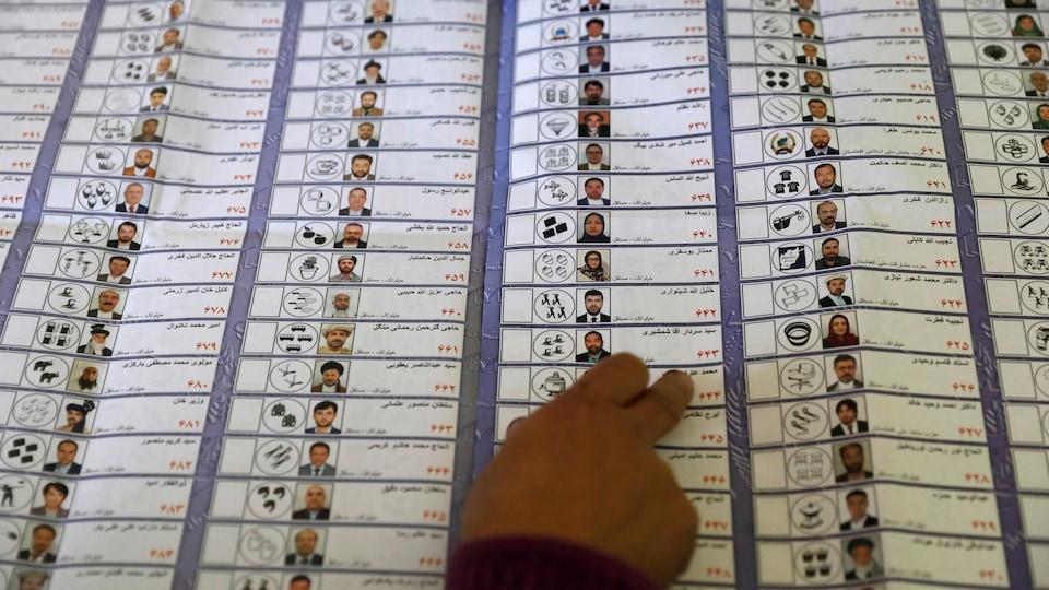Un travailleur électoral afghan compte les bulletins de vote dans le cadre de l'élection législative.