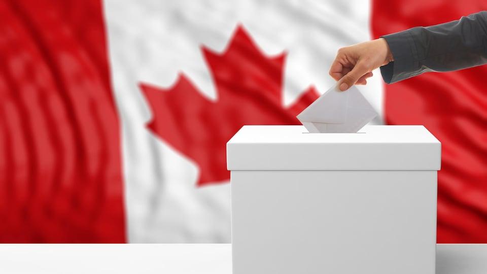 Une main dépose un bulletin de vote dans une boîte de scrutin.