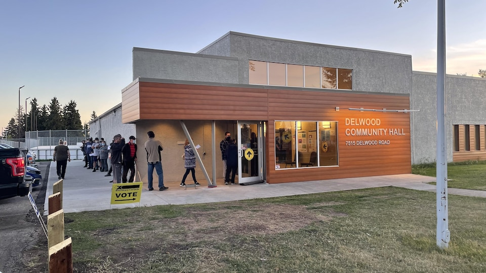 Des gens en file devant le bureau de vote alors que le soleil se couche.