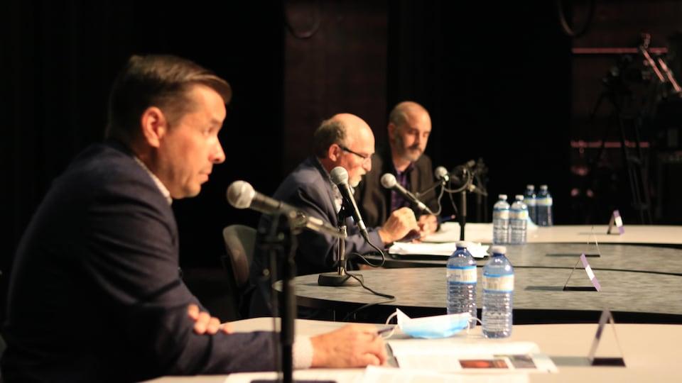 Dans l'ordre, Guy Bernatchez, Jean-Pierre Pigeon et Christian Rioux, tous assis devant un micro.