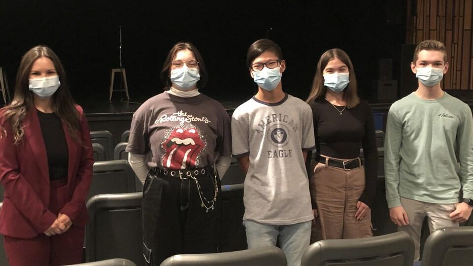 La députée aux côtés de quatre jeunes portant des masques.
