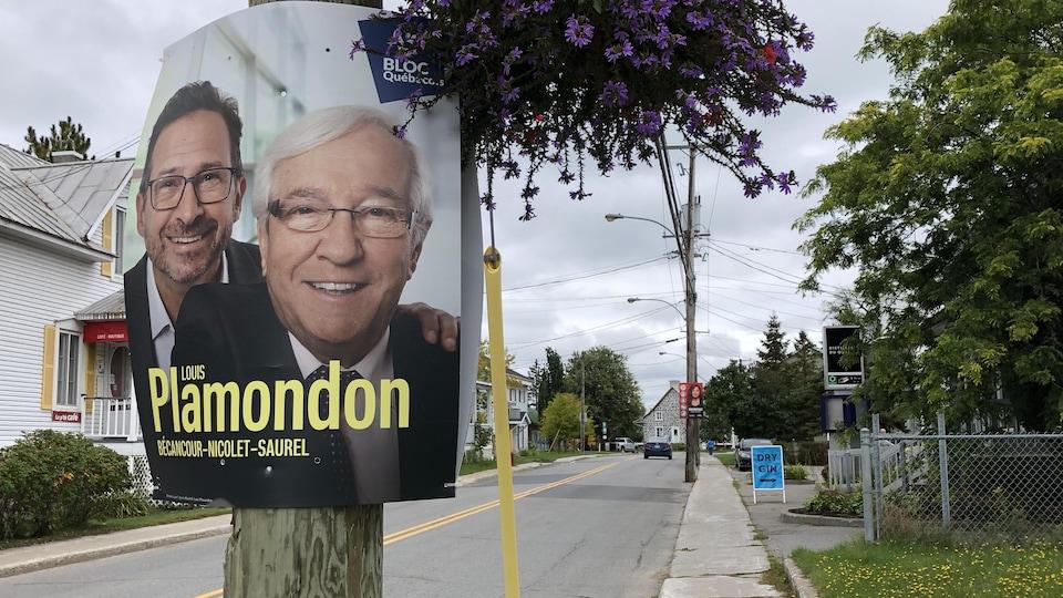 Sur une rue, on aperçoit une pancarte électorale accrochée à un arbre et sur laquelle on voit les visages de Louis Plamondon et de son chef au Bloc québécois Yves-François Blanchet.