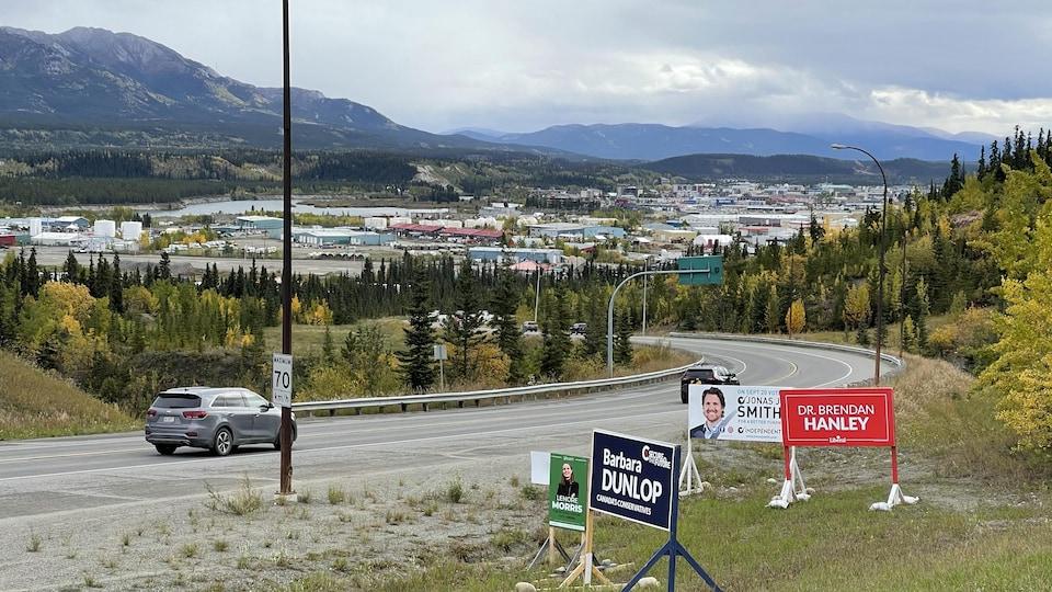 Des pancartes électorales avec la ville de Whitehorse en arrière plan.