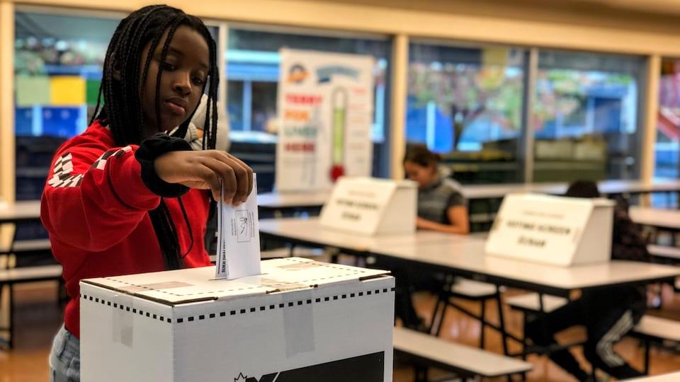 Une jeune fille dépose un bulletin de vote dans une urne. En arrière-plan, deux autres élèves votent dans des isoloirs.