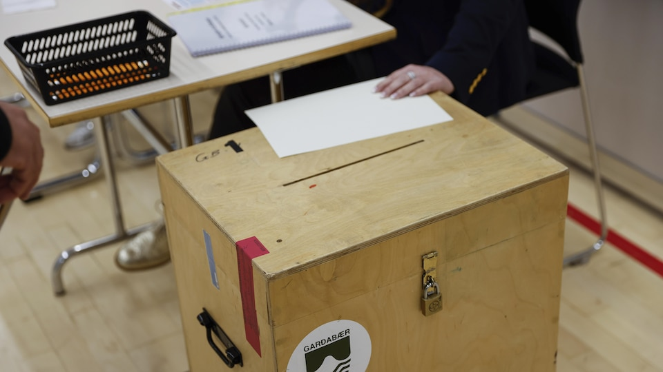 Une boîte de scrutin en bois surveillée par une personne.