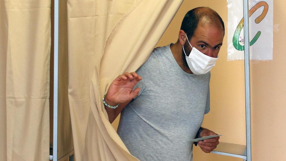 Un homme masqué sortant d'un isoloir avec un bulletin de vote à la main.