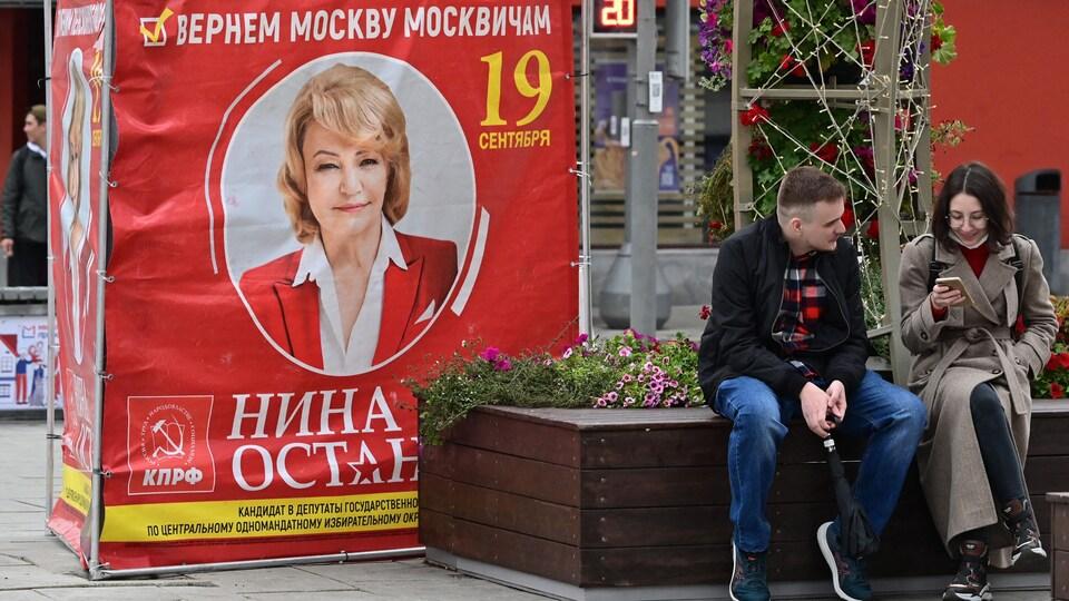 Une affiche rouge avec la photo d'une candidate communiste aux élections législatives en Russie.