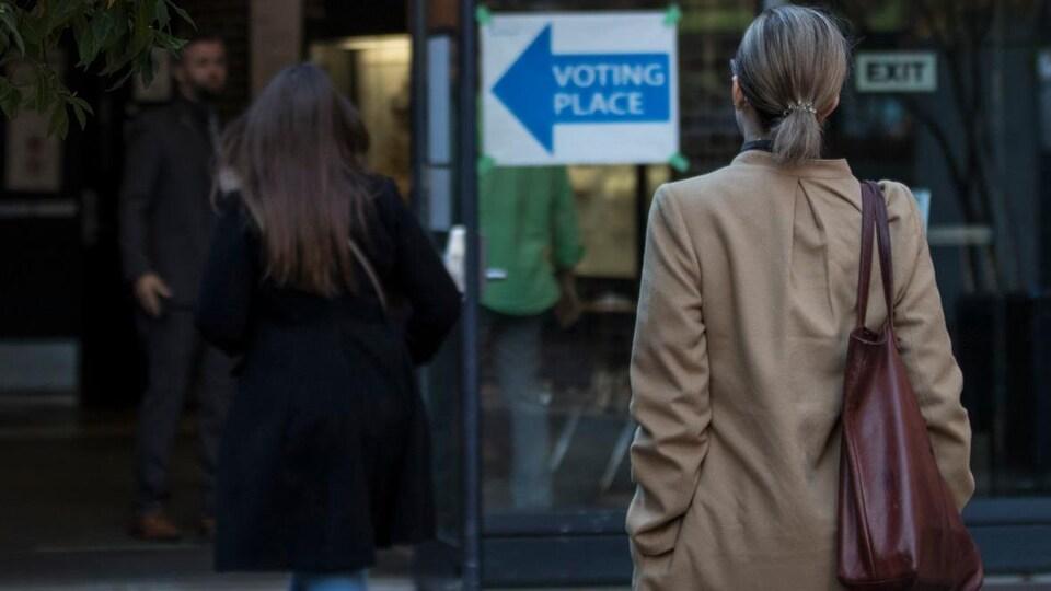 Des électeurs se dirigent vers un bureau de vote. On les voit de dos.