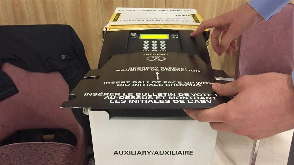 Insertion d'un bulletin de vote dans une tabulatrice au Nouveau-Brunswick