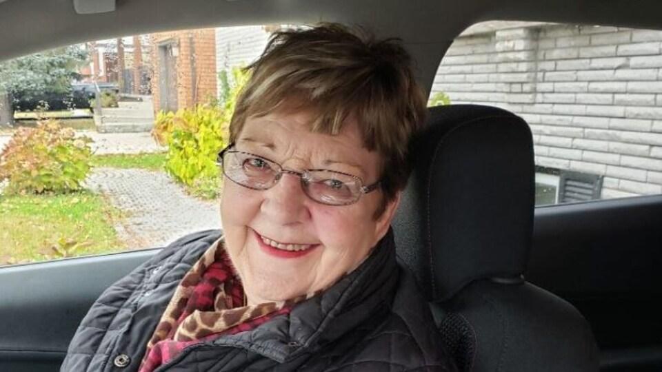 Une femme dans une voiture qui sourit.