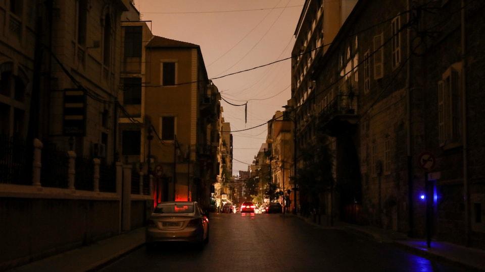 Une rue éclairée seulement par les phares d'une voiture.