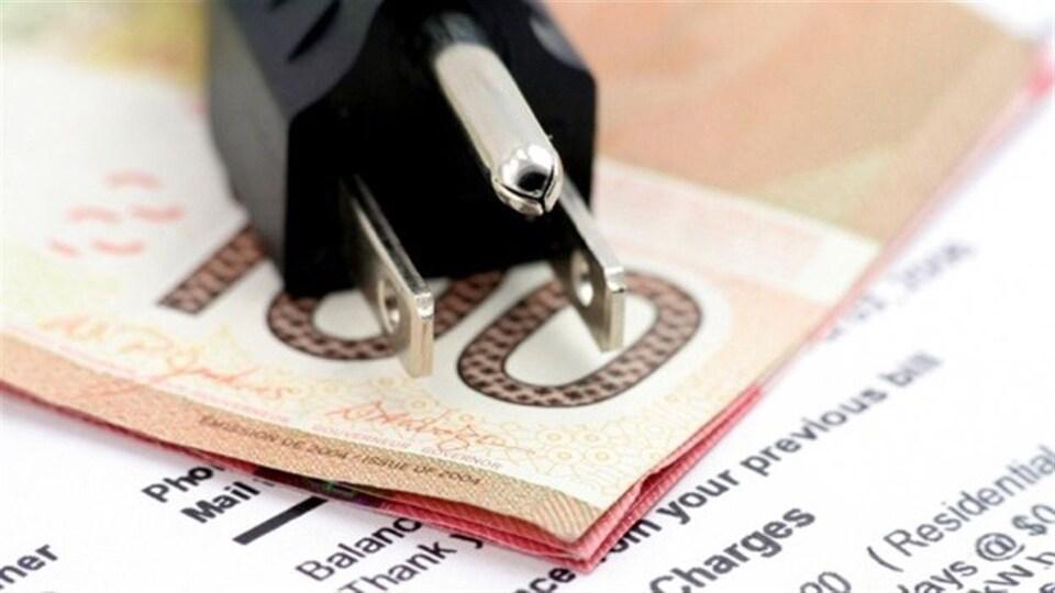 Une fiche électrique, des billets de banque et une facture.