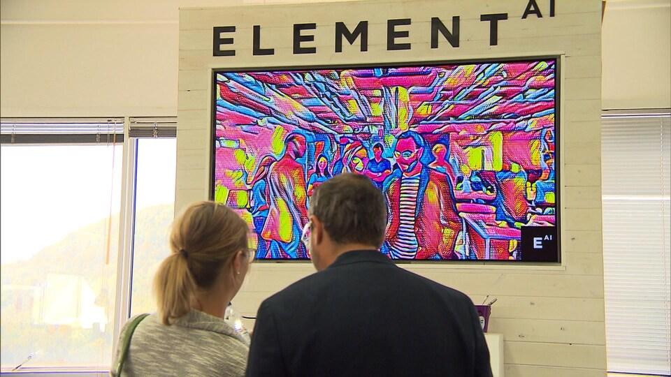 Deux personnes devant une affiche d'Element AI