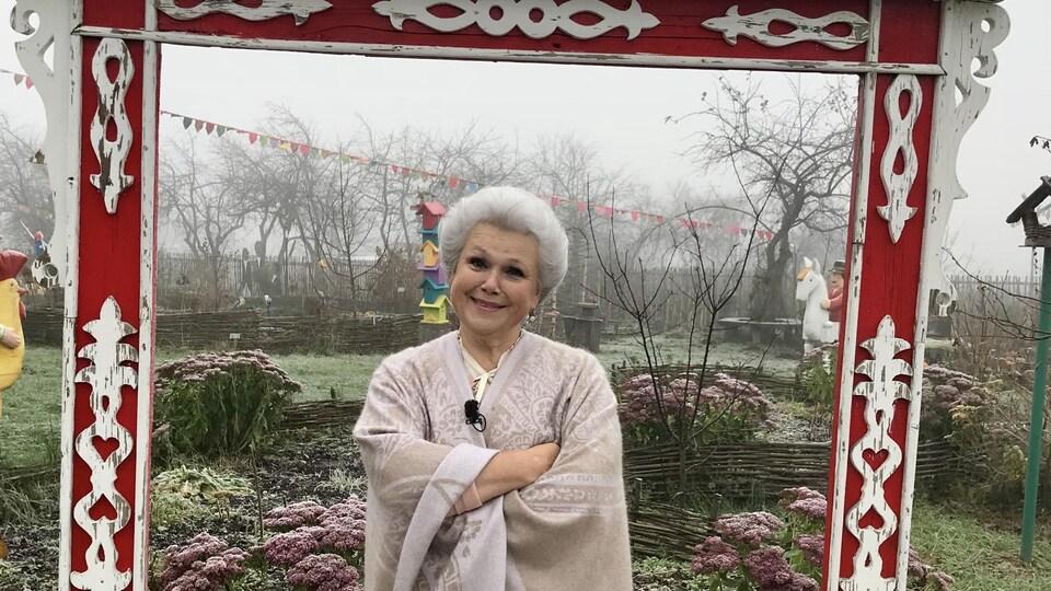 Une dame aux cheveux blancs et chignon est dans son jardin.