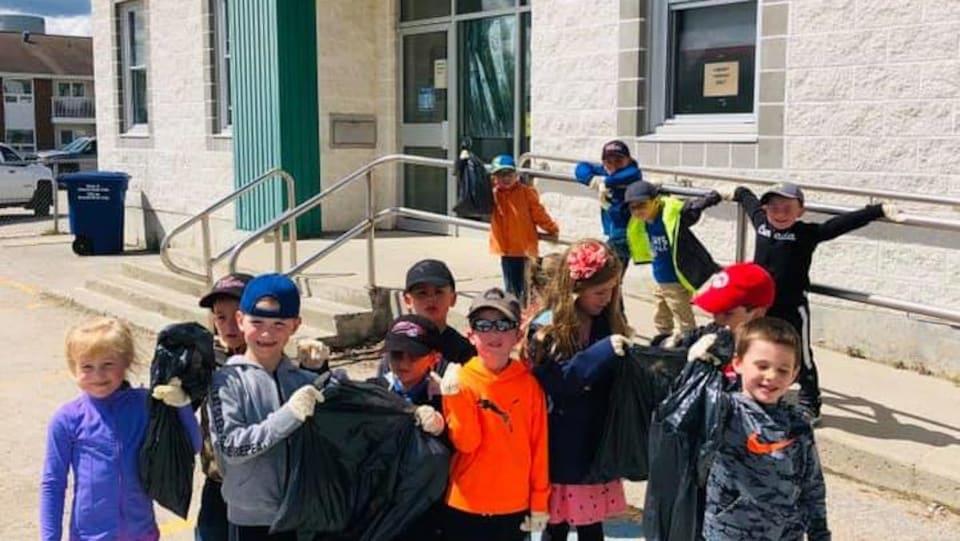 Des élèves de 7 ans avec un sac de poubelle en main